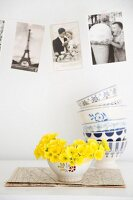 Bowl of primroses below vintage-style postcards on wall