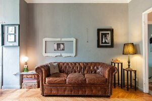 Vintage leather sofa below picture frames on grey-painted wall and table lamps on small side tables