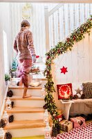Woman carrying lantern up festively decorated staircase