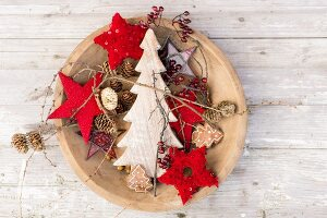Red stars, wooden Christmas trees and pine cones in dish