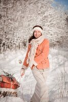 Woman pulling a loaded sledge through a winter landscape