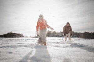 Man and woman having a cheerful snowball fight