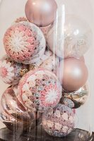 Vintage Christmas baubles with crocheted covers under vintage glass cover