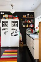 Kitchen with graphic decorations on fridge-freezer against black wall and colourful striped rug on black floor