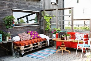 Furniture hand made from pallets and red-painted bench on wooden terrace