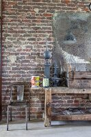 Old workbench and metal chair below patinated mirror on brick wall