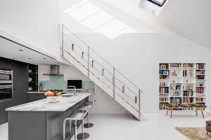Steel staircase leading to gallery level above charcoal-grey designer kitchen in open-plan living area