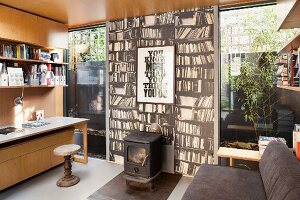 Home office with log burner against photo mural of bookcase in modern extension with floor-to-ceiling windows