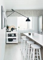 White kitchen counter, bar stools and black cantilever lamp on wall
