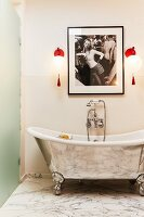 Free-standing, silver bathtub with vintage-style wall-mounted taps below red sconce lamps and feminine photograph