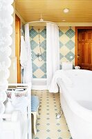 Free-standing white bathtub and shower in bathroom tiled in blue and beige