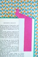 Pink origami bookmark on page of open book