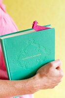 Hand holding book with pink origami bookmark