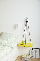 DIY shelf made from climbing ropes hung on wall as bedside table