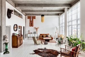 Ribbed concrete ceiling and eclectic furnishings in spacious living area of loft apartment