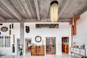 Concrete ceiling, glass wall and eclectic furnishings in loft apartment