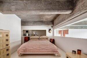 Ribbon window, ethnic art and ribbed concrete ceiling in bedroom