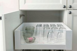 An open kitchen cupboard with glasses in a drawer
