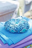 A homemade round pin cushion decorated with ribbon and a bead