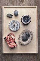 Pebbles, fossil, ribbon and buttons on wooden tray