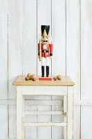 Nutcracker on stool against white board wall