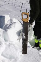 Cutting snow blocks with a saw