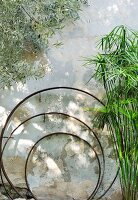 Three nested metal rings next to plants against façade of Mediterranean house
