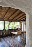 Wooden table, folded folding chairs and traditional tiled floor in Mediterranean dining area