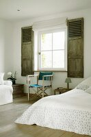 Director's chair on wooden floor in rustic bedroom with interior shutters