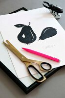 A signed DIY silhouette with a pear design, a pair of scissors and a pink pen