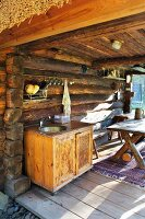 Dining table and outdoor kitchen on terrace of log cabin