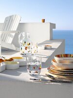 Colourful crockery on white wall with view of sea