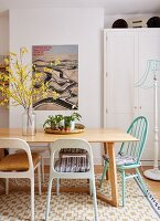 Vase of forsythia on dining table and retro chairs in front of white cupboard