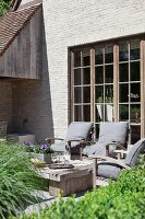 Rustic furniture in pleasant seating area on terrace outside house