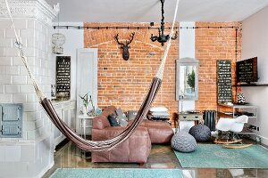 Hammock, concrete wall and tiled stove in living room