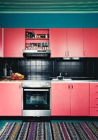Renovated kitchen with red cupboards and black-tiled splashback