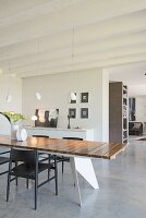 Modern dining table and screed floor in open-plan interior
