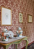 China pots with lids on green console table against ornate wallpaper