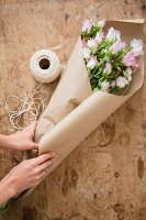 Hands of woman wrapping bouquet in brown paper