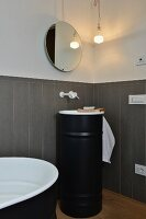 Grey wainscoting, round mirror and black sink unit in modernised bathroom