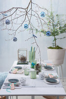 Festive table arrangement with decorated branch