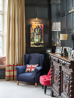Union-flag cushion on blue armchair in living room with panelled walls
