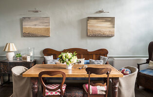 Various chairs and bench around table below maritime pictures on wall