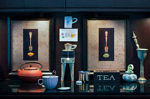 Teapot and cups in front of two illuminated pictures of forks