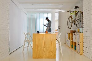 Man in kitchen of small industrial-style maisonette apartment