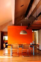 Dining table in front of orange wall below industrial-style gallery