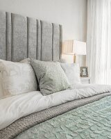 Double bed with elegant bed linen and upholstered headboard