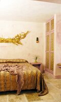 Gold bedspread on double bed below gold hand-crafted artwork in bedroom