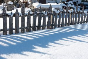 Wooden garden fence in snow
