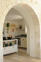 View through traditional arched doorway into modern country-house kitchen